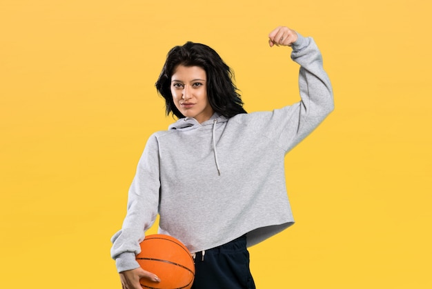 Jovem mulher jogando basquete e comemorando uma vitória