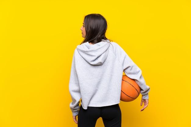 Jovem mulher jogando basquete na parede amarela isolada