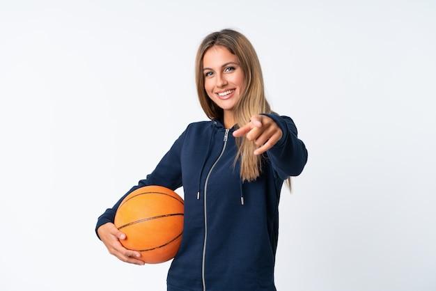 Jovem mulher jogando basquete na parede branca isolada