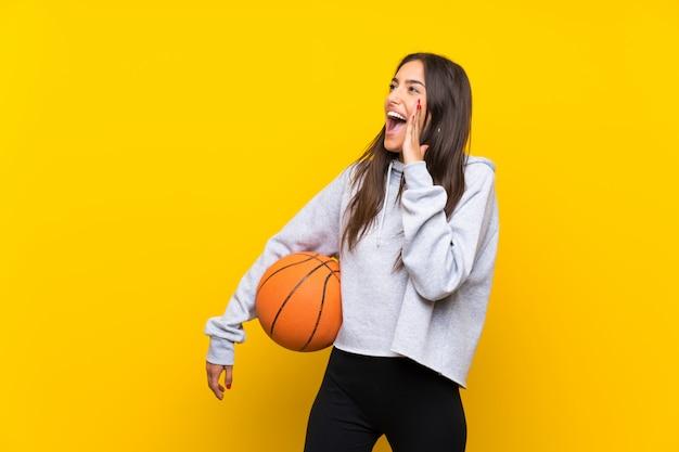 Jovem mulher jogando basquete sobre parede amarela isolada, gritando com a boca aberta