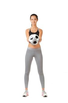 Jovem mulher jogando com uma bola de futebol