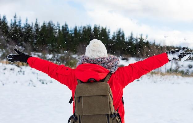 Jovem mulher jogando neve para o ar em um dia ensolarado de inverno, vista traseira. sensação de liberdade e diversão.