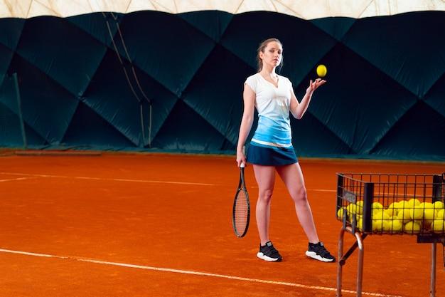 Jovem mulher jogando tênis na quadra de tênis coberta