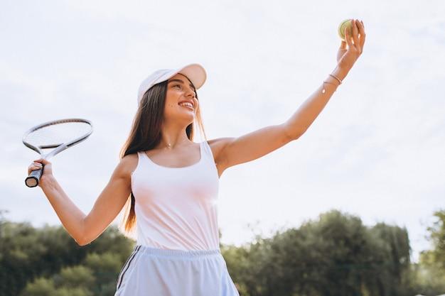 Jovem mulher jogando tênis na quadra