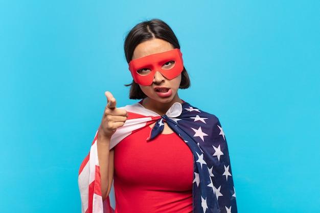 Jovem mulher latina apontando para a câmera com uma expressão agressiva e zangada, parecendo um chefe louco e furioso