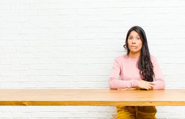Jovem mulher latina bonita olhando confusa e confusa, mordendo o lábio com um gesto nervoso, sem saber a resposta para o problema sentado em frente a uma mesa