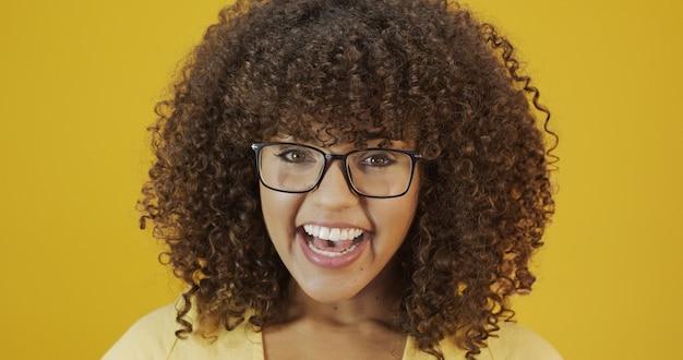 Jovem mulher latina com cabelos cacheados, feliz com seus óculos. conceito de cuidados com os olhos.