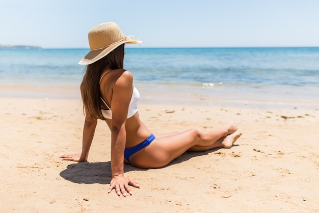 Jovem mulher latina com chapéu de palha sentada na praia do mar