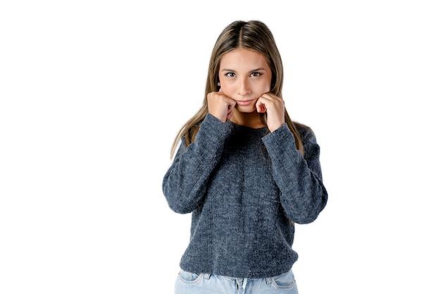 Jovem mulher latina com uma cara de beicinho e punhos nas laterais do rosto em um fundo branco puro. fotografia de estúdio.