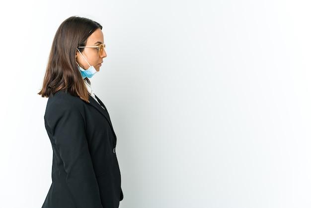 Jovem mulher latina de negócios usando uma máscara para se proteger de cobiçoso isolado na parede branca, olhando para a esquerda, pose de lado.