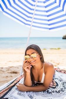 Jovem mulher latina deitada na areia sob o guarda-sol na praia do mar. vocação de verão