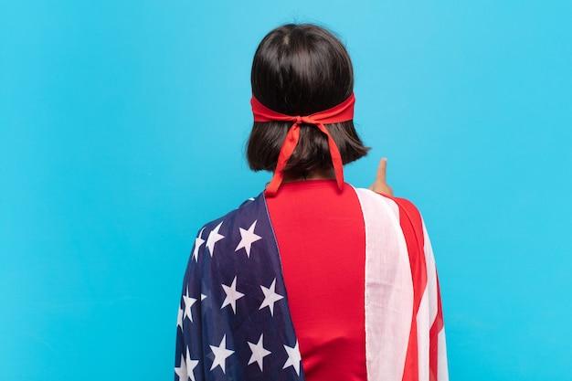 Jovem mulher latina em pé e apontando para um objeto no espaço da cópia, vista traseira