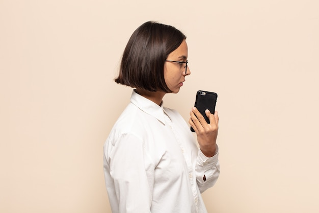 Jovem mulher latina em vista de perfil, olhando para copiar o espaço à frente, pensando, imaginando ou sonhando acordada