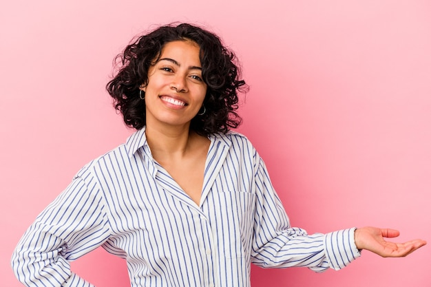 Jovem mulher latina encaracolada isolada em fundo rosa, mostrando uma expressão de boas-vindas.