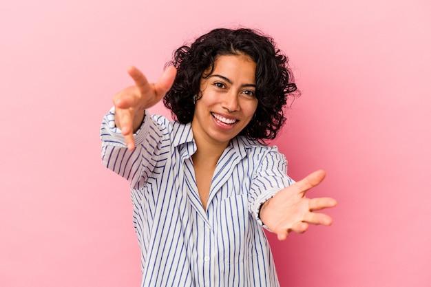 Jovem mulher latina encaracolada isolada em um fundo rosa se sente confiante em dar um abraço para a câmera.