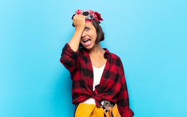 Jovem mulher latina erguendo a palma da mão na testa pensando oops, depois de cometer um erro estúpido ou lembrar, sentindo-se burra