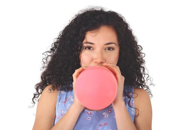 Jovem mulher latina está soprando balão