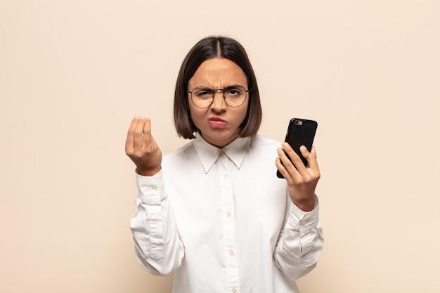 Jovem mulher latina fazendo capice ou gesto de dinheiro, mandando você pagar suas dívidas!