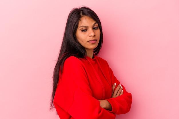 Jovem mulher latina isolada em fundo rosa suspeita, incerta, examinando você.