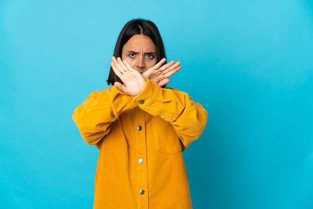 Jovem mulher latina isolada em um fundo azul fazendo gesto de parada com a mão para interromper um ato Foto Premium
