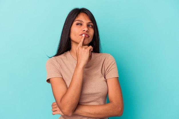 Jovem mulher latina isolada em um fundo azul infeliz olhando na câmera com expressão sarcástica.