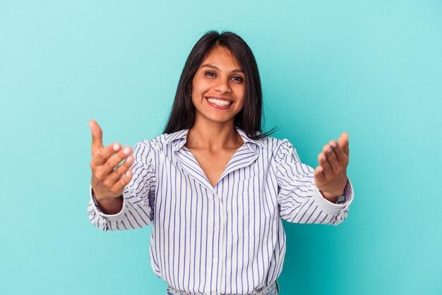 Jovem mulher latina isolada em um fundo azul, mostrando uma expressão de boas-vindas.