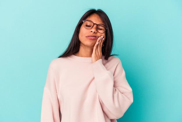 Jovem mulher latina isolada em um fundo azul, tendo uma forte dor nos dentes, dor molar.