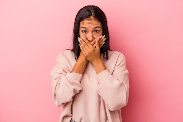 Jovem mulher latina isolada em um fundo rosa, cobrindo a boca com as mãos parecendo preocupadas.