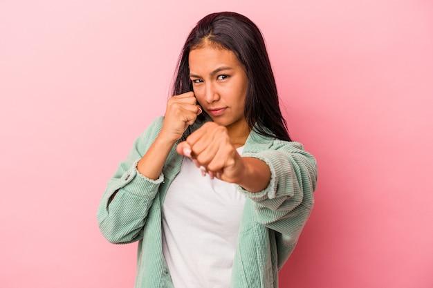 Jovem mulher latina isolada em um fundo rosa dando um soco, raiva, lutando devido a uma discussão, boxe.