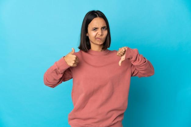 Jovem mulher latina isolada na parede azul, fazendo sinais de bom-ruim. indeciso entre sim ou não