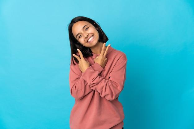 Jovem mulher latina isolada na parede azul sorrindo e mostrando o sinal da vitória