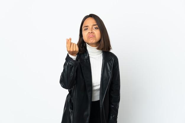 Jovem mulher latina isolada na parede branca fazendo gesto italiano