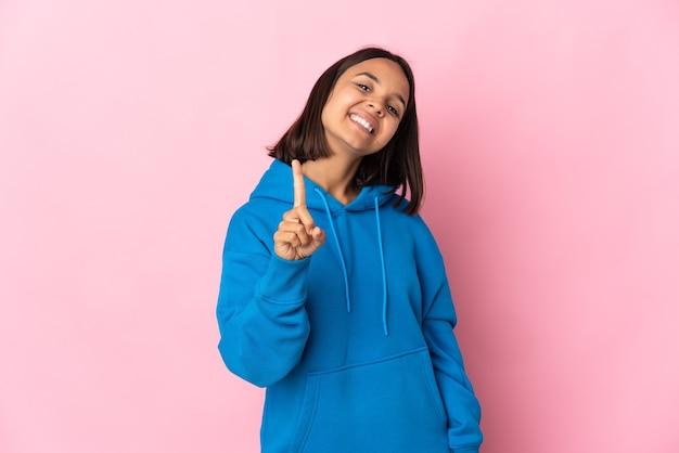 Jovem mulher latina isolada na parede rosa mostrando e levantando um dedo