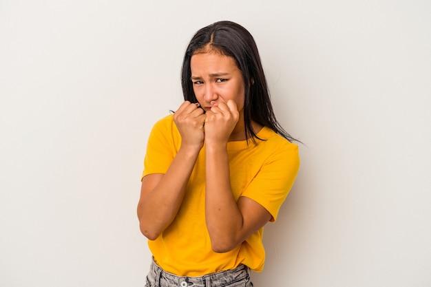 Jovem mulher latina isolada no fundo branco dando um soco, raiva, lutando devido a uma discussão, boxe.