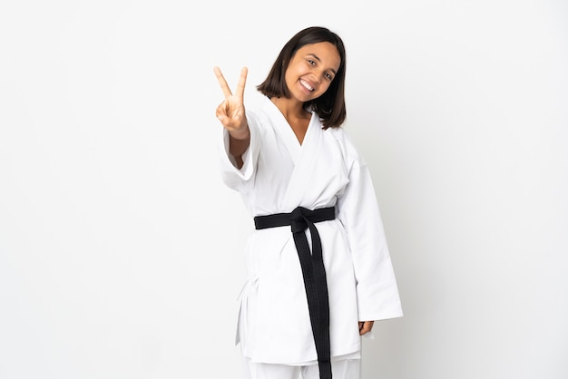 Jovem mulher latina isolada no fundo branco sorrindo e mostrando o sinal da vitória