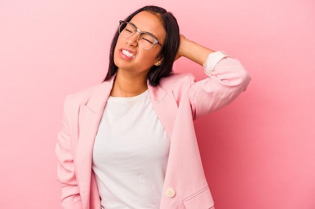 Jovem mulher latina isolada no fundo rosa, cansada e com muito sono, mantendo a mão na cabeça.