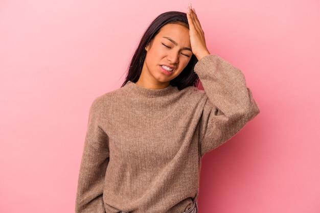 Jovem mulher latina isolada no fundo rosa, esquecendo de algo, batendo na testa com a palma da mão e fechando os olhos.