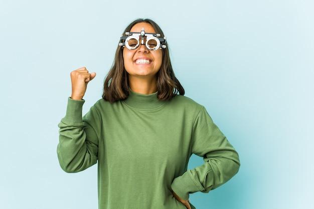 Jovem mulher latina oculista sobre parede isolada comemorando uma vitória, paixão e entusiasmo, expressão feliz.