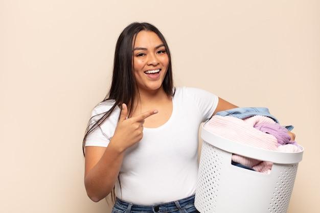 Jovem mulher latina parecendo animada e surpresa, apontando para o lado e para cima para copiar o espaço