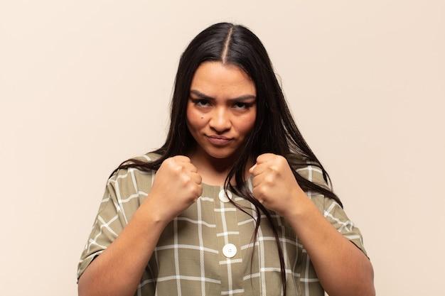Jovem mulher latina parecendo confiante, zangada, forte e agressiva, com punhos prontos para lutar em posição de boxe