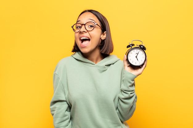Jovem mulher latina parecendo feliz e agradavelmente surpresa, animada com uma expressão de fascínio e choque