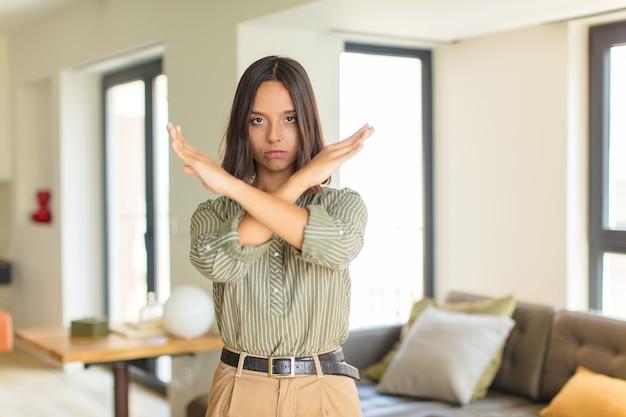 Jovem mulher latina parecendo irritada e cansada de sua atitude, dizendo o suficiente! mãos cruzadas na frente, dizendo para você parar