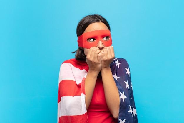 Jovem mulher latina parecendo preocupada, ansiosa, estressada e com medo, roendo as unhas e olhando para o espaço da cópia lateral