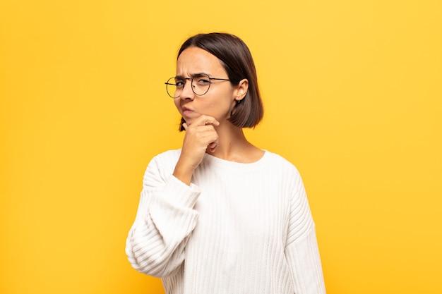 Jovem mulher latina parecendo séria, pensativa e desconfiada, com um braço cruzado e a mão no queixo, opções de peso