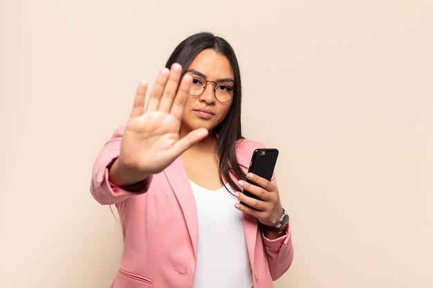 Jovem mulher latina parecendo séria, severa, descontente e irritada, mostrando a palma da mão aberta fazendo gesto de pare
