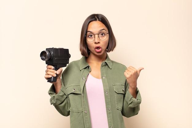 Jovem mulher latina parecendo surpresa em descrença, apontando para um objeto ao lado e dizendo uau, inacreditável
