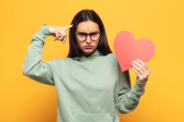 Jovem mulher latina se sentindo confusa e intrigada, mostrando que você está louco, louco ou fora de si