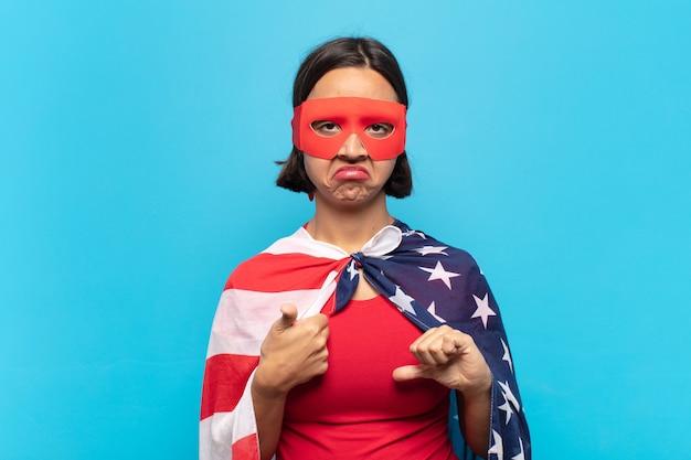 Jovem mulher latina se sentindo confusa, sem noção e insegura, avaliando o que há de bom e de ruim em diferentes opções ou escolhas