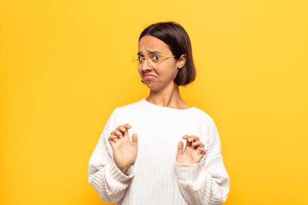 Jovem mulher latina se sentindo enojada e com náuseas, se afastando de algo desagradável, fedorento ou fedorento, dizendo eca
