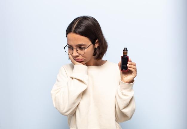 Jovem mulher latina se sentindo entediada, frustrada e com sono depois de uma tarefa cansativa, enfadonha e tediosa, segurando o rosto com a mão